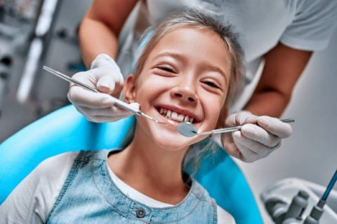 Young girl at dentist. Dentist hans with dental treatment. Close up view. Front view