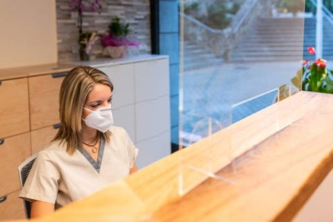 female receptionist from a dentist center behind a reception desk with a translucent screen.