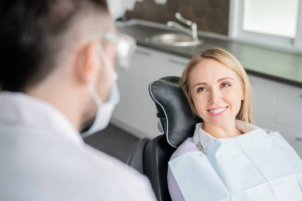 Happy young blonde female patient looking at her dentist with healthy smile while sitting in armchair before examination