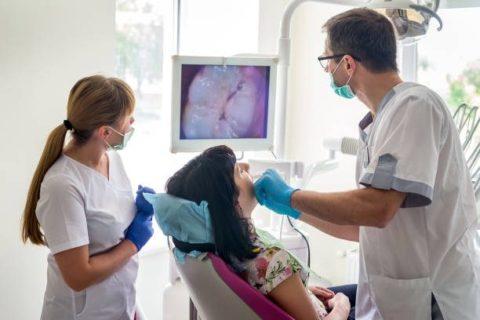 Doctor examining patient's teeth with intraoral camera